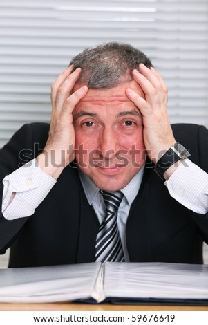 Business man with a head ache and red face - stock photo