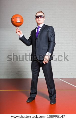 Business man with basketball. Wearing dark sunglasses. Good looking young man with short blond hair. Gym indoor. - stock photo