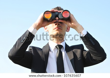 Business man with binoculars on sky - stock photo