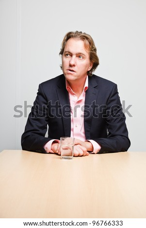 Business man with blond hair sitting bored behind table with glass of water in office isolated on white background - stock photo