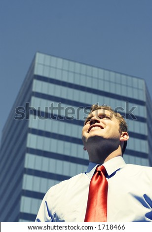 Business man with blue shirt and red tie is smiling in front of large, blue business building - stock photo