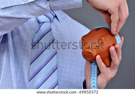 Business man with brown piggy bank and measure tape - stock photo
