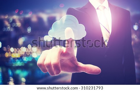 Business man with cloud computing concept on blurred city background - stock photo