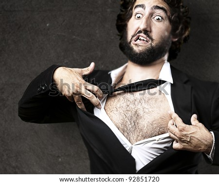 business man with courage and superman concept tearing off his shirt against a grunge wall - stock photo