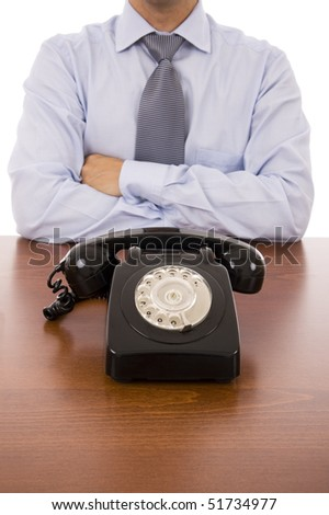 Business man with crossed arms waiting for a call - stock photo