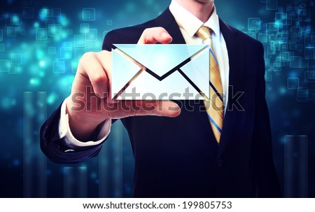 Business man with email envelopes on blue technology background - stock photo