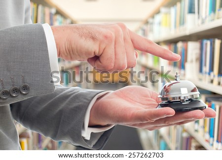 Business man with grey suit. He is using hotel bell. Over library background - stock photo
