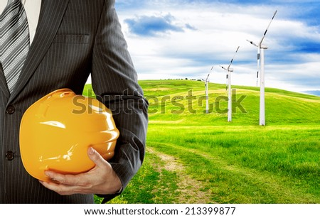 Business man with hardhat standing in electricity park. Alternative energy and construction project of development.   - stock photo