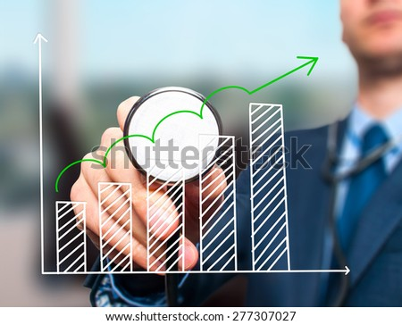 Business man with stethoscope examining graph, business analysis. Isolated on office. Business, technology, health, finance concept. Stock Photo - stock photo