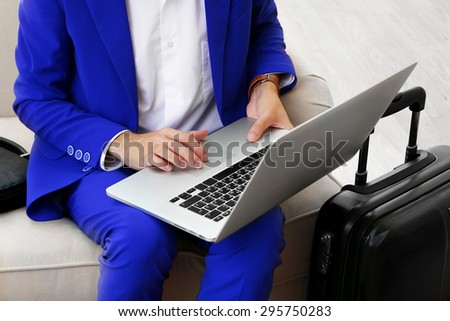 Business man with suitcase and laptop sitting on sofa in hall - stock photo