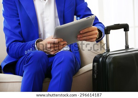 Business man with suitcase and tablet sitting on sofa in hall - stock photo