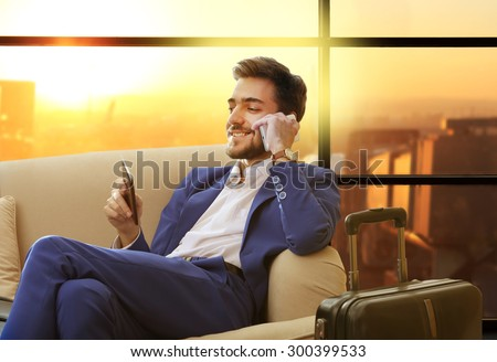 Business man with suitcase in hall of airport - stock photo