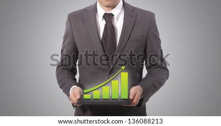 business man with touch screen graph on a tablet, grey background. - stock photo