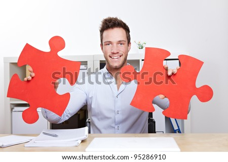 Business man with two oversized red jigsaw puzzle pieces in office - stock photo