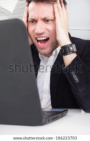 business man working and having problem with using laptop looking at screen and holding his head with both hands, businessman sitting at the desk, computer virus or error concept - stock photo