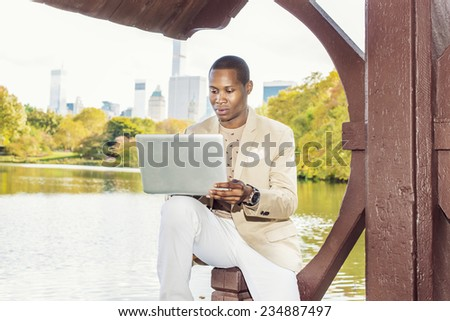 Business Man Working. Dressing in cream blazer, collarless sweater, white pants, wearing a wristwatch, a young black guy is sitting by a lake in a big city, looking down, working on laptop computer. - stock photo