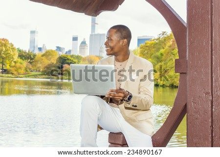 Business Man Working. Dressing in cream blazer, collarless sweater, white pants, wearing a wristwatch, a young black guy is sitting by lake in big city, smiling, thinking, working on laptop computer. - stock photo