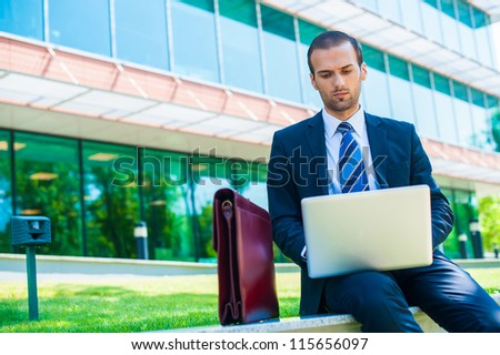 business man working on his laptop or notebook computer outdoors - stock photo
