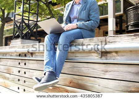 business man working  with  a laptop,  sitting outside - stock photo