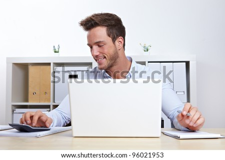 Business man working with laptop and calculator in office - stock photo
