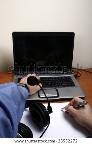 Business man working with the computer and writing with headphones on the table - stock photo