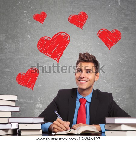 business man writing a love letter at his office desk - stock photo