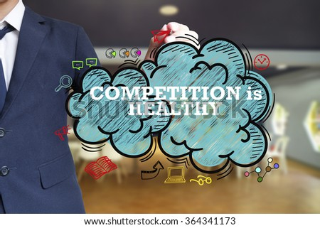 business man writing COMPETITION IS HEALTHY over the cloud with office background , business concept , business idea - stock photo
