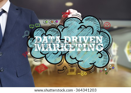 business man writing DATA DRIVEN MARKETING over the cloud with office background , business concept , business idea - stock photo