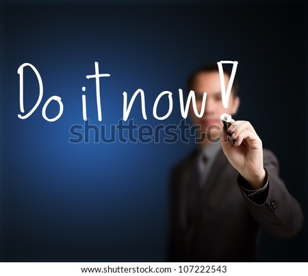 business man writing do it now - stock photo