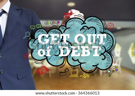 business man writing GET OUT OF DEBT over the cloud with office background , business concept , business idea - stock photo