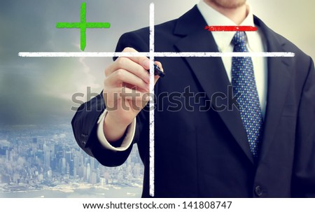 Business man writing pros and cons with big city backdrop - stock photo