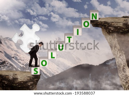 Business manager bring puzzle solution on mountain top - stock photo