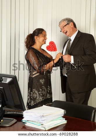 Business manager giving a heart shaped lollipop to his Assistant on Secretary Day - stock photo