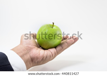 Business market share and success concept.Green apple on businessman hand. - stock photo
