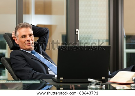 Business - mature boss contemplating in his office - stock photo