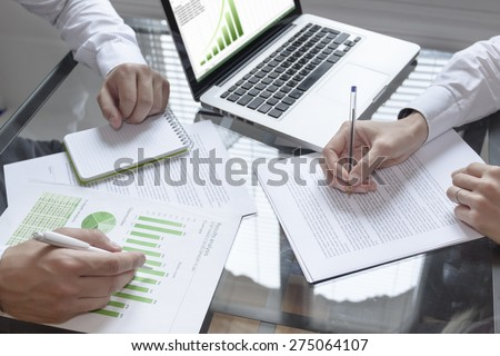 Business meeting about sustainable development with laptop and notepad - stock photo