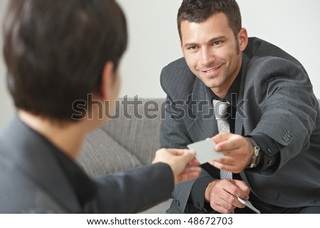 Business meeting at office lobby, people sitting on sofa changing business cards. - stock photo