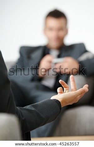 Business meeting at office. People sitting on sofa, talking. Focus on explaining female hand. - stock photo