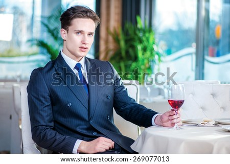 Business meeting at the restaurant. Confident businessman in formal wear sitting at a table in a restaurant while holding a glass of wine and looking at the camera - stock photo