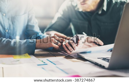 Business meeting concept. Photo young businessmans crew working with new startup project in modern loft. Generic design smartphone holding female hands. Horizontal, film effect - stock photo