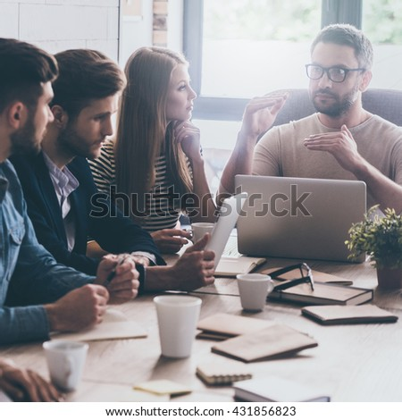 Business meeting. Confident mature man in eyeglasses gesturing while sitting together with his colleagues at the desk in office  - stock photo