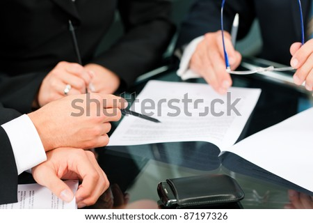 Business - meeting in an office; lawyers or attorneys (only hands) discussing a document or contract agreement - stock photo