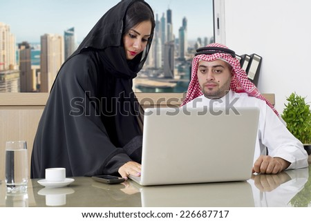 Business Meeting in office , arabian businessman & arabian Secretary wearing hijab working on laptop - stock photo