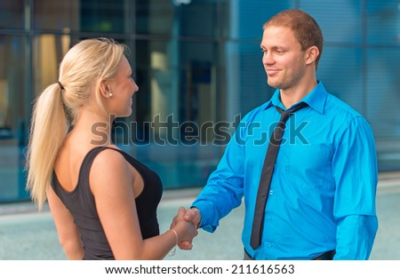 Business meeting. Man and woman shaking hands outdoors. - stock photo