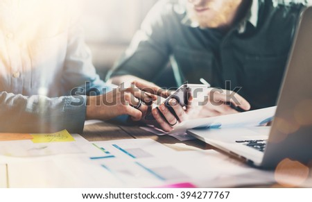 Business meeting partners. Photo young businessmans crew working with new startup project in modern loft. Generic design smartphone holding female hands. Horizontal, film effect - stock photo