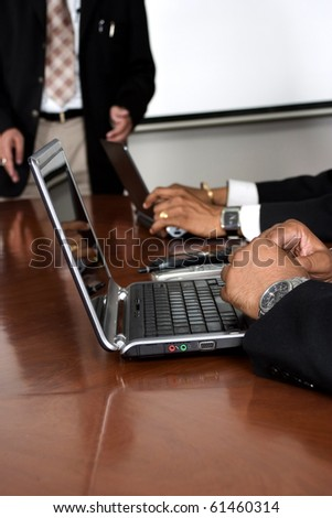 Business Meeting  shallow depth of field, focus is on the first man's hand and laptop - stock photo