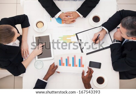 Business meeting. Top view of business people in formalwear sitting at the table and discussing something - stock photo