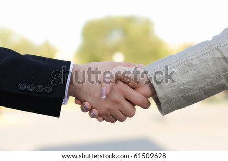 Business men and women shaking hands on a light background - stock photo