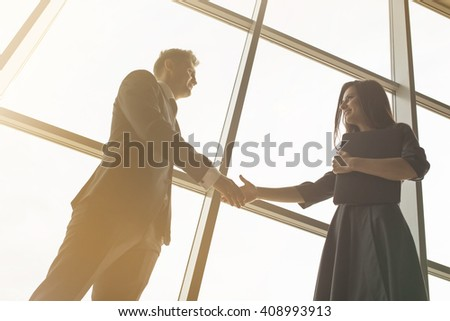 Business men and women shaking hands with a smile on the background of the large panoramic windows in a modern business center. Models dressed in a dark business suits. - stock photo