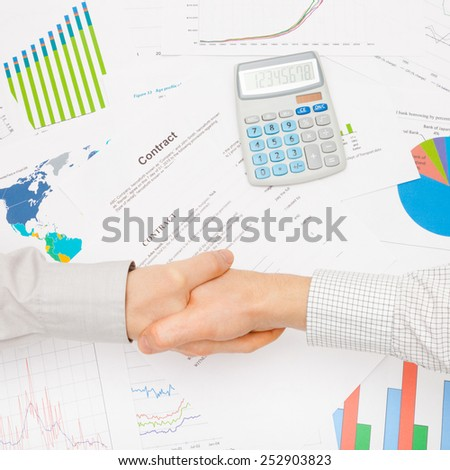 Business men in office - shaking hands over contract - stock photo
